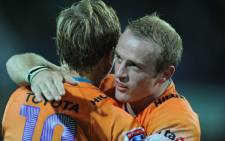 FILE. Cheetahs halfback Sarel Pretorius (R) congratulates teammate Joe Pietersen (L). Picture: AFP/ Greg Wood.