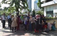 Indonesians wait outside an office building after a 6.4 magnitude quake hit Jakarta on 23 January 2018. Picture: AFP