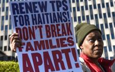 "Immigrant advocates rally against ""DHS decision to terminate TPS for Haitians"" during a rally on 21 November 2017 in New York. Picture: AFP"