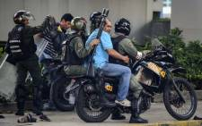 An anti-government activist is arrested by the National Guard during clashes in Caracas on 27 July 2017 on the second day of a 48-hour general strike called by the opposition in Venezuela. Picture: AFP.