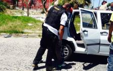 FILE: Cape Town police officers search suspects in Manenberg after gang warfare flared up on the Cape flats. Picture: Shamiela Fisher/EWN.