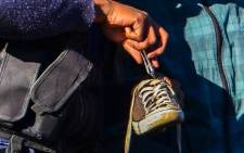 Police search a man's shoe for drugs, during a police operation in Westbury, Johannesburg, on 26 June 2013. Picture: Michelle Lubbe/EWN.