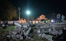 Onlookers and medias stand amidst the debris in the aftermath of the deadly fire explosion that rocked the Hindu Goddess, Puttingal Devi Temple in Paravur, 60kms North-West of Thiruvananthapuram in Kerala on the late evening of 10 April, 2016. Picture: AFP.
