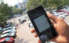 A file picture showing an India man showing the Uber app to book the three wheeler in New Delhi, India. Picture: EPA/Harish Tyagi.