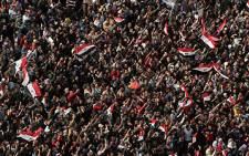Egyptian demonstrators wave national flags and shout slogans in Cairo's Tahrir square on 25 November 2011. Picture: AFP