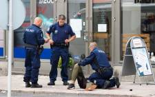 Police officers stand next to a person lying on the pavement in the Finnish city of Turku where several people were stabbed on 18 August 2017. Picture: AFP.