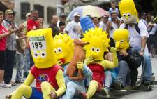 COLOMBIA, Medellín : Participants dressed as The Simpsons TV series characters descend a hill in a homemade car during the XXIII Car Festival in Medellin, Antioquia department, Colombia, on October 7, 2012. AFP PHOTO/Raul ARBOLEDA