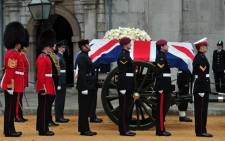 The Bearer Party made up of personnel from the three branches of the military stand alongside the coffin of British former prime minister Margaret Thatcher on a gun carriage to be drawn by the King's Troop Royal Horse Artillery during her ceremonial funeral at the Church of St Clement Danes in central London on April 17, 2013.  Picture: AFP.