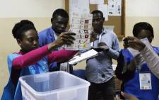 A polling station official shows a ballot during the counting of votes at the end of the general election in Luanda on 23 August 2017. Picture: AFP.