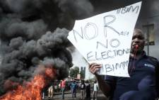 An opposition supporter holds a placard during their protest on 11 October 2017. Picture: AFP.