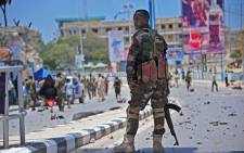 A member of Somalia's security services patrols the scene of a suicide car bomb blast on 30 August, 2016 in Mogadishu. Picture: AFP