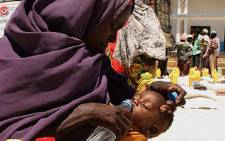 FILE: An internally displaced woman from southern Somalia gives water to her daughter at a distribution centre in Mogadishu in 2011. Picture: AFP.
