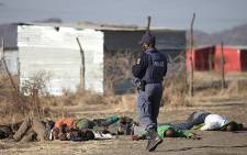 Police look over at Lonmins Marikana mine workers who were protesting on 16 August, 2012 for more wages. Picture: Taurai Maduna/Eyewitness News.