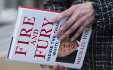 """FILE: A man holds a copy of the book 'Fire and Fury: Inside the Trump White House' by Michael Wolff in Washington on 5 January 2018. President Trump has decried the instant best-seller as """"phony"""" and """"full of lies."""" Picture: AFP."""