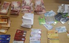 Cards and cash seized by Northern Cape police from an alleged money launderer in Prieska. Picture: @SAPoliceService/Twitter