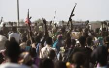 A Sudan Peoples Liberation Army (SPLA) soldier waves his AK-47 as soldiers celebrate alongside Internally Displaced People (IDP) outside the United Nations Mission in the Republic of South Sudan (UNMISS) base in Malakal after the SPLA claimed it had recaptured the town from rebels on 19 March 2014. Picture: AFP.