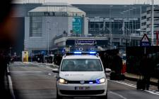 FILE: A Belgian police vehicle drives past passengers who are evacuating the Brussels Airport of Zaventem after twin blasts rocked the main terminal on 22 March 2016. Picture: AFP.