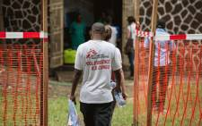 Doctors Without Borders (Medecins sans frontiere - MSF) team members walk through an Ebola security zone at the entrance of the Wangata Reference Hospital in Mbandaka, northwest of DR Congo on 20 May 2018. Picture: AFP