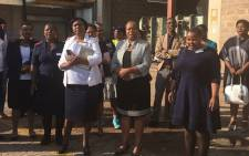 Gauteng Health MEC Gwen Ramokgopa (centre) leads a short burial service for 41 of the 42 unidentified bodies which were transported in an open trailer last week. Picture: Thando Kubheka/EWN.