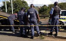 Police clear the scene after two officers were shot and wounded by four men on 5 February 2013. Picture: Mbali Sibanyoni/EWN