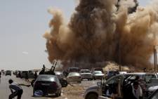 Libyan rebel fighters take cover as a bomb dropped by an airforce fighter jet explodes near a checkpoint on the outskirts of Ras Lanuf. Picture: AFP