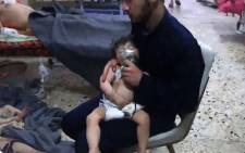 An image grab taken from a video released by the Syrian civil defence in Douma shows unidentified volunteers giving aid to children at a hospital following an alleged chemical attack on the rebel-held town on 8 April 2018. Picture: AFP.