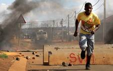 A young boy runs away from an approaching police Nyala dispersing protestors in Simunye Township in the west rand. Service delivery protest spilt over from neighbouring Bekkersdal on 24 October 2013. Picture: Sebabatso Mosamo/EWN