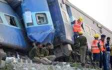 Indian rescue workers search for survivors in the wreckage of a train that derailed near Pukhrayan in Kanpur district on November 20, 2016. A passenger train derailed in northern India on November 20, killing at least 107 travellers most of whom were sleeping when the fatal accident occurred, police said. Rescue workers rushed to the scene near Kanpur in Uttar Pradesh state where the Patna-Indore express train derailed in the early hours of the morning. Picture: AFP.