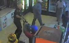 A screen grab from graphic footage released by Crime Line of three armed men shooting a Coin security guard at a Roodepoort filling station on 18 September 2013.