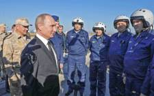 Russian President Vladimir Putin (2nd-L) and Russian Defence Minister Sergei Shoigu (L) meet with Russian air force pilots during their visit to the Russian air base in Hmeimim in the northwestern Syrian province of Latakia on 11 December 2017.  Picture: AFP.