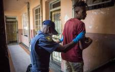 A man is searched by police inside a hijacked building during Operation Fiela 2. Picture: Thomas Holder/EWN