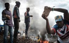 Opposition supporters hold up bricks as they block streets and burn tyres during a protest in Kisumu, Kenya, on 11 October 2017. Picture: AFP.