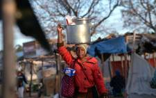 A female vendor cooking food is on her way in Jambanja market in Seke, 58km south of Harare. Picture: Alexander Joe / AFP.
