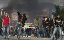 Palestinian protestors throw stones towards Israeli security forces at Hawara checkpoint, south of the West Bank city of Nablus, during clashes following a demonstration against US President Donald Trump's decision to recognise Jerusalem as the capital of Israel on 7 December 2017. Picture: AFP