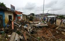 Residents look at water damaged businesses along a roadside in Abidjan on 19 June 2018, after floodwaters receded following an overnight downpour in the city. Picture: AFP