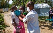 A handout picture taken on 20 October 2017 and released by Medecin sans Frontieres shows a doctor helping a little girl to put on her protective mask at the health centre plague triage and treatment centre in Toamasina. Picture: MSF/AFP.