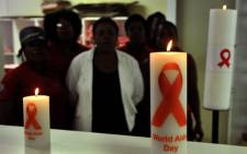 FILE: Health workers observing World AIDS Day, posing behind candles commemorating. Picture: AFP.