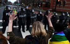 An anti-Trump protester holds her hands up as police officers lineup in Washington, DC, on January 20, 2107. Picture: AFP.