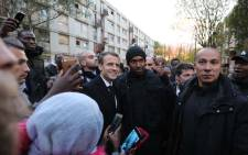 French President Emmanuel Macron (C) poses for pictures as he meets residents of the Cite du Chene Pointu during his visit focused on the theme of urban planing in Clichy-sous-Bois, northern Paris, on 13 November 2017. Picture: AFP
