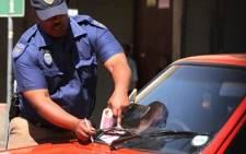 A Johannesburg Metro Police officer writes a parking ticket outside the Johannesburg High Court. Picture: EWN.