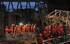 Workers search through the remains of a collapsed platform in a cooling tower at a power station at Fengcheng in China's Jiangxi province on 24 November, 2016. Picture: AFP.