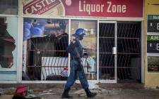 A police officer walks outside a looted liquor store in Coligny in the North West after protests in the town on 25 April 2017 over the death of a young boy. Picture: Reinart Toerien/EWN