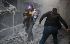A Syrian man carries two children in the rubble of buildings following regime air strikes on the rebel-held besieged town of Douma in the eastern Ghouta region, on the outskirts of the capital Damascus, on 7 February 2018. Picture: AFP.