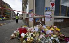 A Police officer stands on duty beyond flowers laid at a cordon on Borough High Street, near Borough Market in London on 5 June 2017, as they continue their investigations following the 3 June terror attack. British police made several arrests in two dawn raids following the 3 June London attacks, claimed by the Islamic State group which left seven people dead. Picture: AFP.