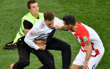 A striker is evacuated from the football pitch by security guards and Croatia's defender Dejan Lovren (R) during the Russia 2018 World Cup final football match between France and Croatia at the Luzhniki Stadium in Moscow on 15 July 2018. Picture: AFP.