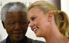 Former President Nelson Mandela with Oscar winner Charlize Theron in March 2004 in Johannesburg. Picture: AFP.