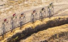 Riders cast shadows on the gravel track shortly after sunrise during Stage 1 of the 2016 Absa Cape Epic. Picture: Aletta Harrison/EWN