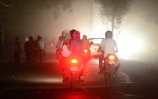 Indian commuters battle through a dust storm in Allahabad on 13 May 13 2018. Picture: AFP.