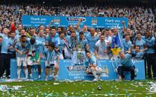 The Manchester City squad pose for pictures with the trophy after they won the Premiership title race following a 2-0 victory in the English Premier League football match between Manchester City and West Ham United at the Etihad Stadium in Manchester on May 11, 2014. Picture: AFP.