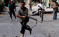 A Libyan rebel fighter dashes over a street to evade sniper fire in Zawiya, west of Tripoli, as rebel forces staged an assault on regime forces in the city's main square on August 19, 2011. Picture: AFP